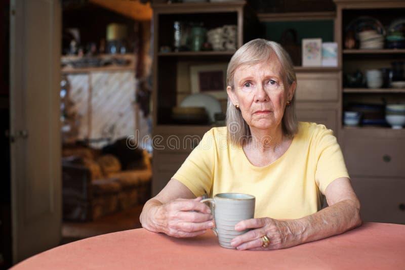Donna senior con l'espressione depressa immagine stock