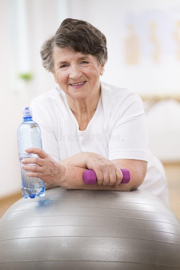 Donna senior con la bottiglia di acqua e testa di legno che si appoggia palla relativa alla ginnastica grigia fotografia stock libera da diritti