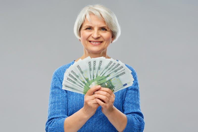 Donna senior con le centinaia di euro banconote dei soldi immagine stock