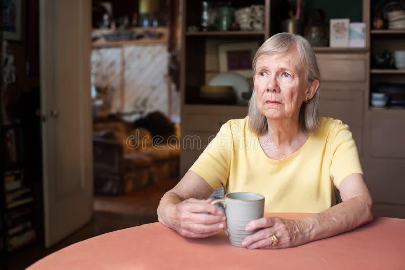 Donna senior con lo sguardo fisso in bianco fotografia stock