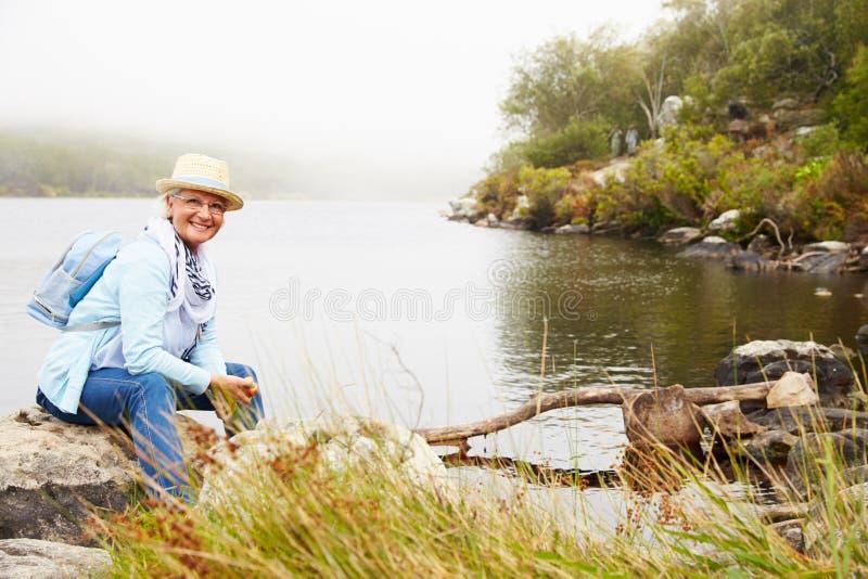 Donna senior con un cappello che si siede da un lago, sorridente alla macchina fotografica fotografia stock libera da diritti