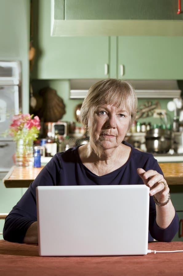 Donna senior con un computer portatile immagine stock libera da diritti