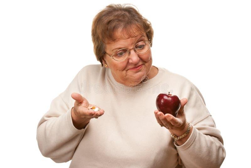 Donna senior confusa che tiene Apple e le vitamine fotografie stock