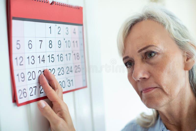 Donna senior confusa con demenza che esamina il calendario murale immagine stock