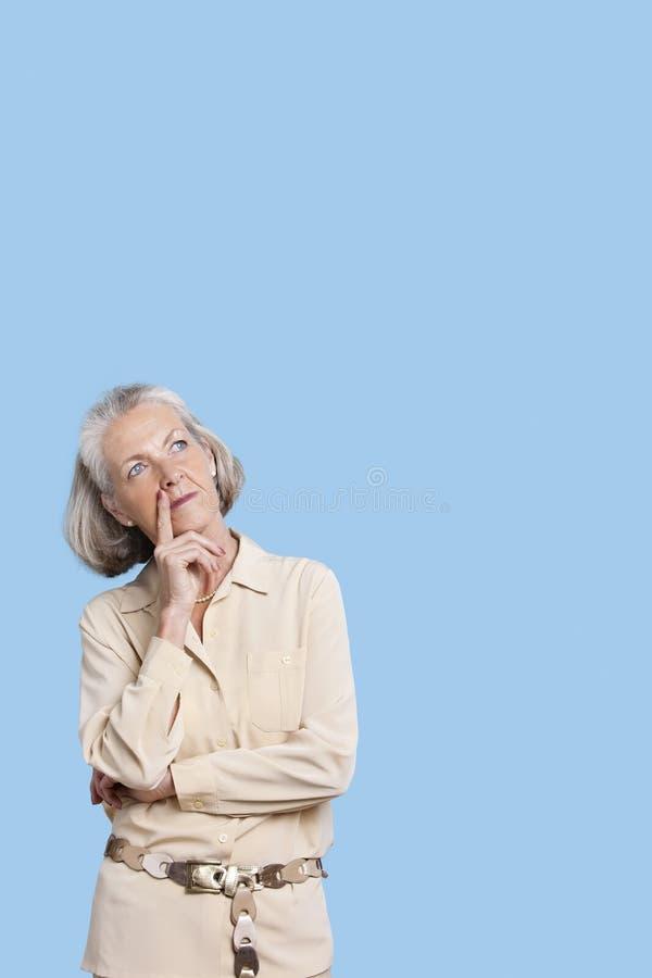 Donna senior contemplativa in casuale con la mano sul mento contro fondo blu immagini stock
