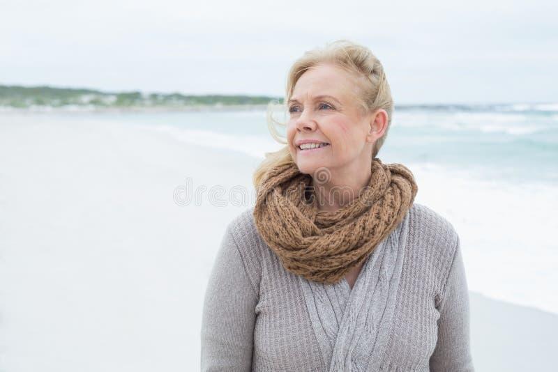Donna senior contemplativa che distoglie lo sguardo spiaggia fotografia stock