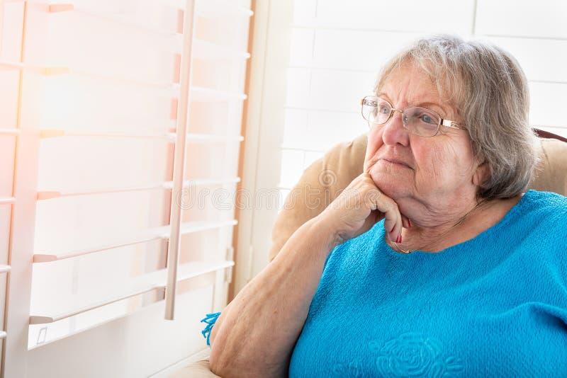 Donna senior contemplativa che guarda fisso dalla sua finestra fotografia stock