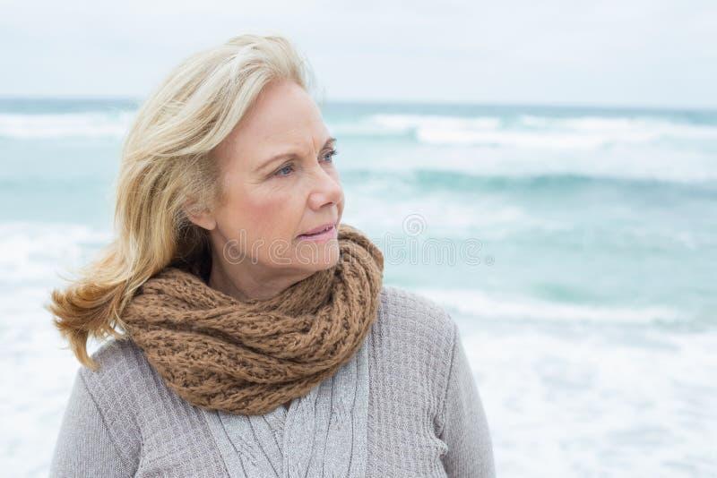 Donna senior contemplativa che si rilassa alla spiaggia immagini stock