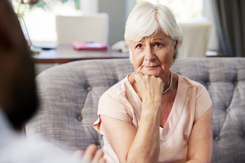 Donna senior depressa che ha terapia con lo psicologo immagini stock libere da diritti