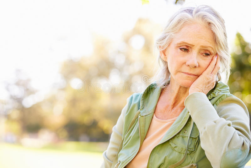 Donna senior depressa che si siede fuori immagini stock
