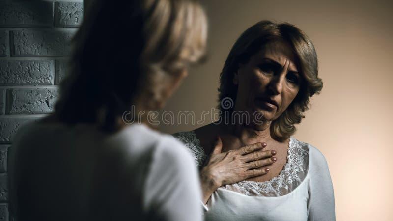 Donna senior deprimente che esamina riflessione in specchio, cancro di pelle, preoccupazioni fotografie stock