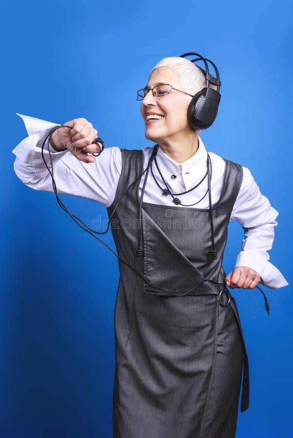 Donna senior di affari che balla al battito della musica fotografia stock libera da diritti