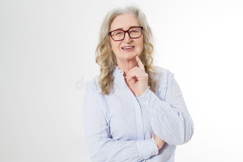 Donna senior di affari con i vetri alla moda ed il fronte della grinza isolato su fondo bianco Signora in buona salute matura Cop fotografia stock libera da diritti
