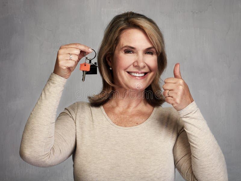 Donna senior di agente immobiliare con la chiave fotografie stock