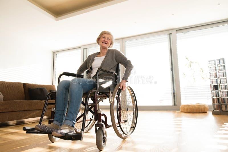 Donna senior disabile in sedia a rotelle a casa in salone immagini stock libere da diritti