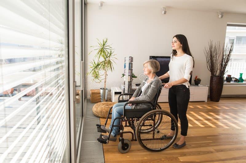Donna senior disabile in sedia a rotelle con il suo giovane daugher immagine stock