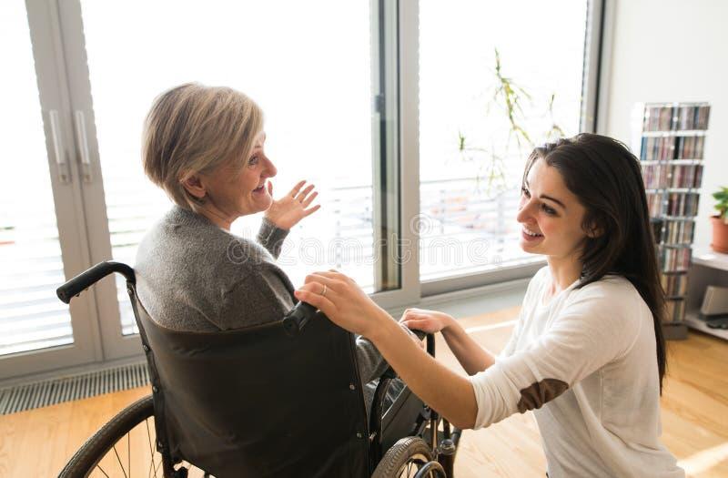 Donna senior disabile in sedia a rotelle con il suo giovane daugher fotografia stock libera da diritti