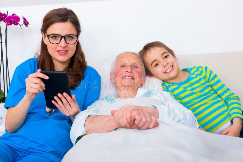 Donna senior divertendosi con la famiglia e medico fotografia stock libera da diritti