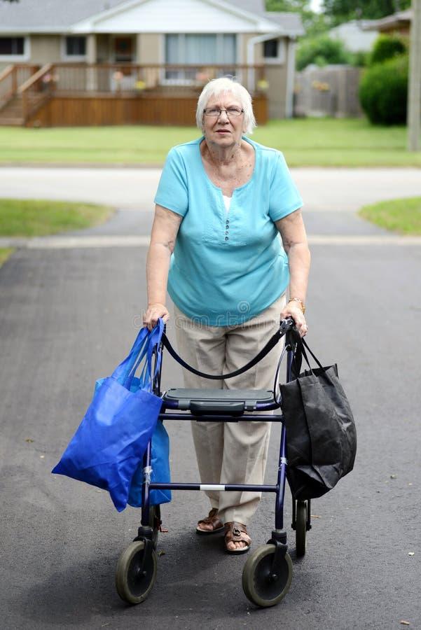 Donna senior e camminatore sovraccaricati di sacchetti della spesa fotografie stock