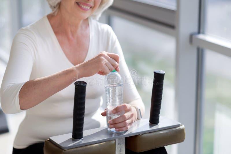 Donna senior esile allegra che ha acqua dopo l'allenamento della palestra fotografia stock libera da diritti