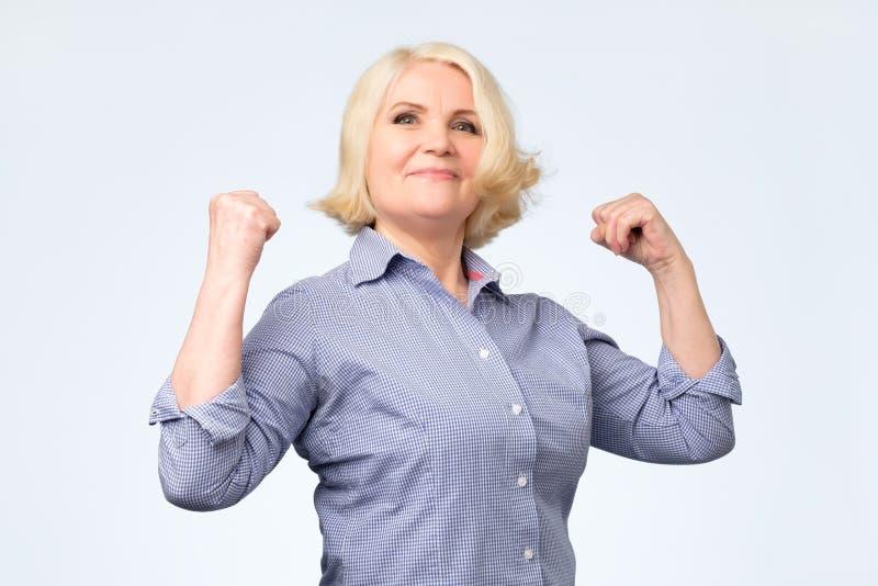 Donna senior felice anziana che è fiera di se stessa che mostra i suoi muscoli immagine stock libera da diritti