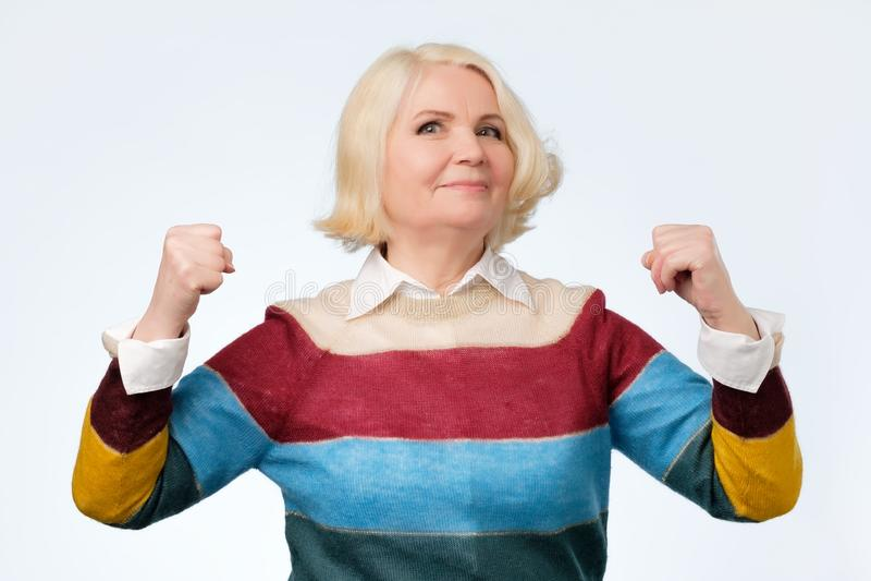 Donna senior felice anziana che è fiera di se stessa che mostra i suoi muscoli immagini stock libere da diritti