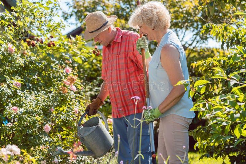 Donna senior felice attiva che sta accanto al suo marito durante il lavoro del giardino immagini stock libere da diritti