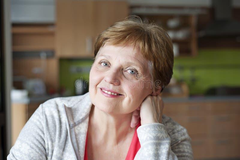 Donna senior felice a casa che si rilassa fotografia stock