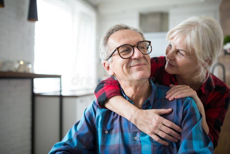 Donna senior felice che abbraccia il suo marito fotografie stock