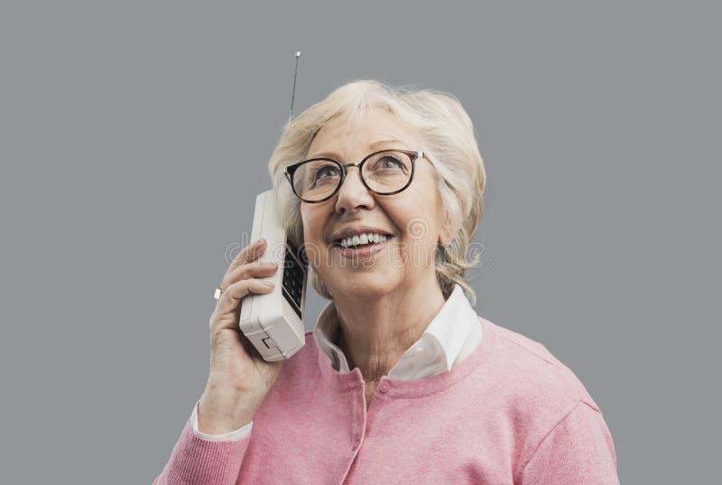 Donna senior felice che parla con un vecchio telefono fotografia stock