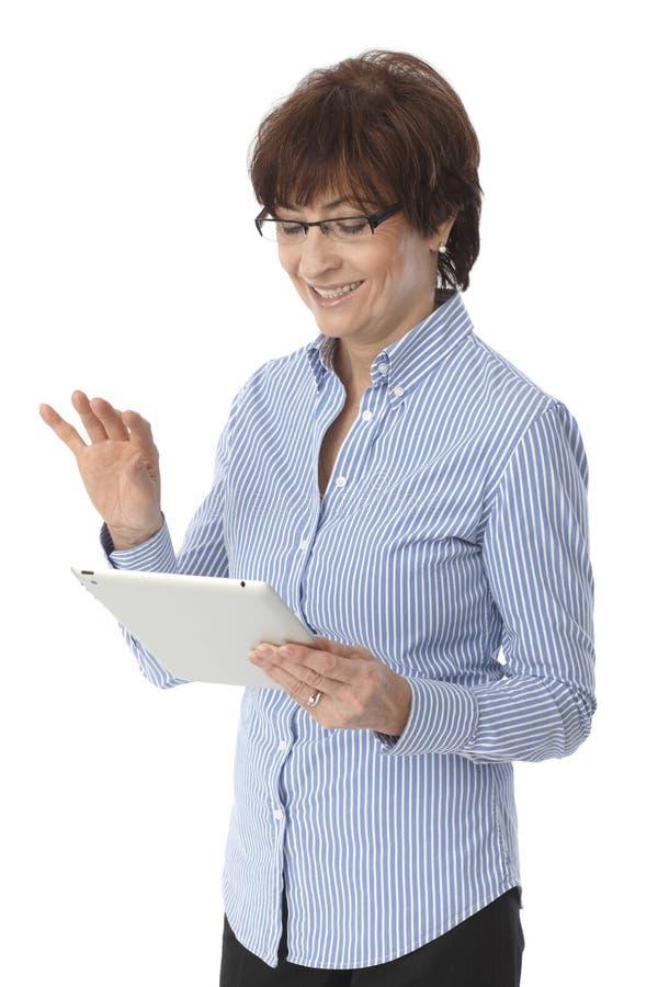 Donna senior felice che per mezzo del computer della compressa fotografia stock libera da diritti
