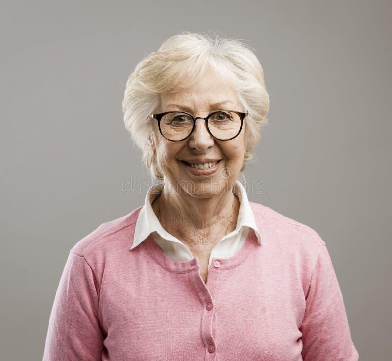 Donna senior felice che posa sul fondo grigio immagini stock libere da diritti