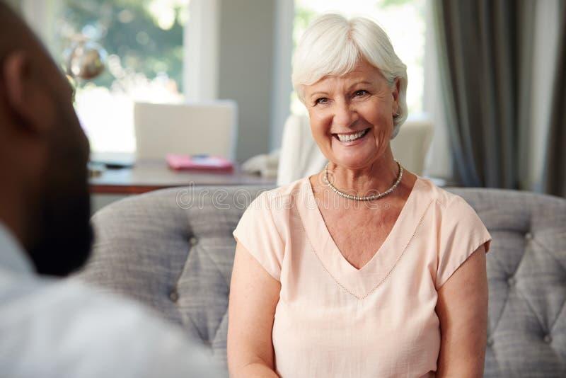 Donna senior felice che prende consiglio finanziario a casa fotografie stock libere da diritti