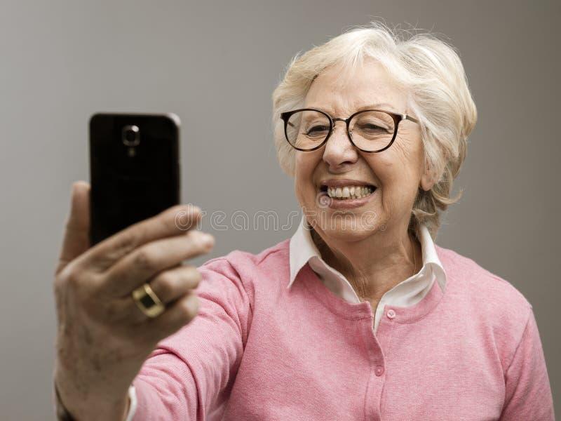 Donna senior felice che prende i selfies con il suo smartphone immagini stock