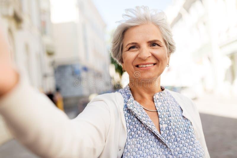 Donna senior felice che prende selfie sulla via della città immagine stock