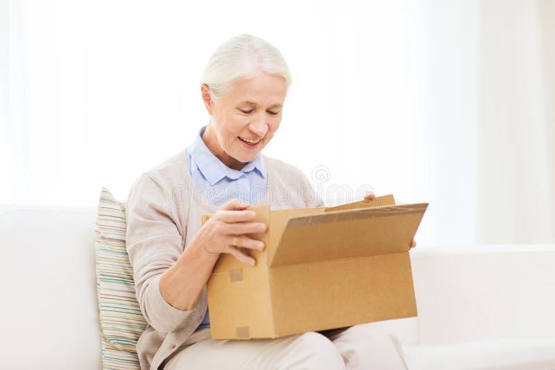 Donna senior felice con la scatola del pacchetto a casa immagini stock libere da diritti