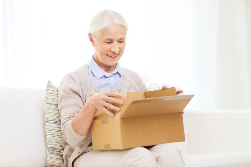Donna senior felice con la scatola del pacchetto a casa fotografie stock libere da diritti