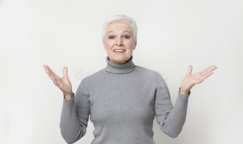 Donna senior felice sorpresa che tira le mani verso la macchina fotografica per accogliere fotografie stock