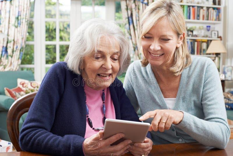 A donna senior femminile del vicino mostrando come utilizzare la compressa di Digital immagini stock libere da diritti