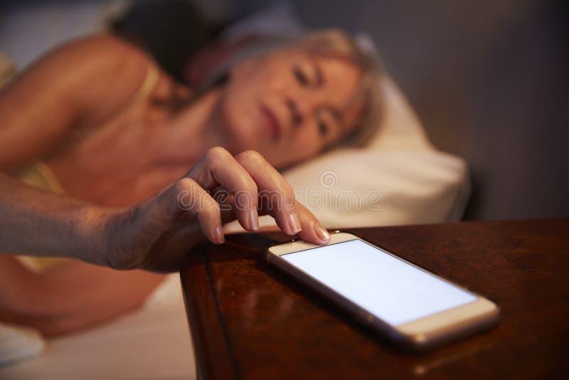 Donna senior insonne a letto alla notte che controlla telefono cellulare fotografie stock