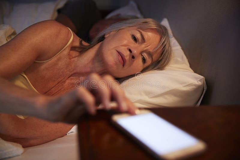 Donna senior insonne a letto alla notte che controlla telefono cellulare immagini stock libere da diritti