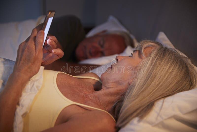 Donna senior insonne a letto alla notte facendo uso del telefono cellulare immagine stock