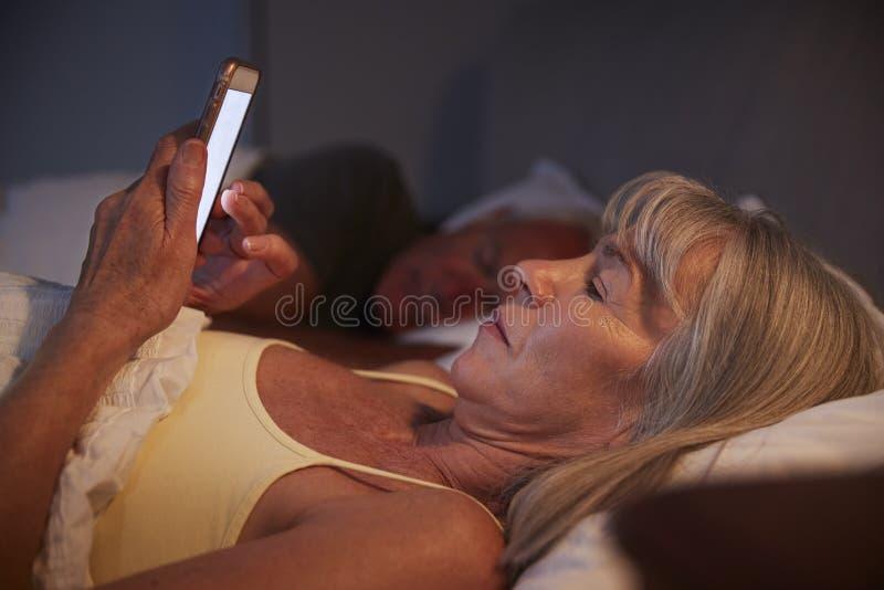 Donna senior insonne a letto alla notte facendo uso del telefono cellulare fotografie stock