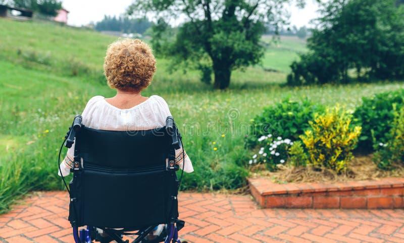 Donna senior irriconoscibile in una sedia a rotelle immagine stock