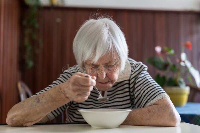 Donna senior isolata che mangia il suo pranzo a casa di riposo fotografia stock libera da diritti