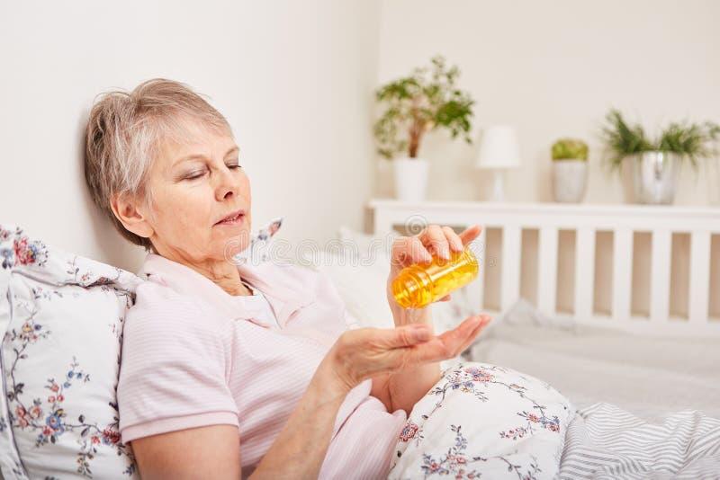 Donna senior malata con il medicinale fotografie stock libere da diritti