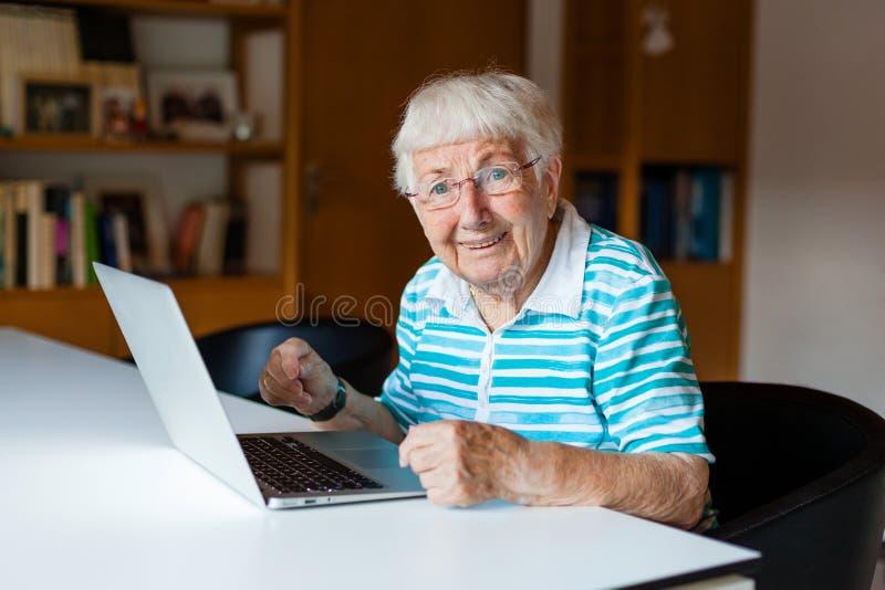 Donna senior molto anziana che per mezzo di un computer fotografia stock libera da diritti