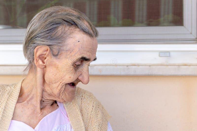 Donna senior molto anziana che si siede nel balcone un giorno di estate fotografie stock libere da diritti