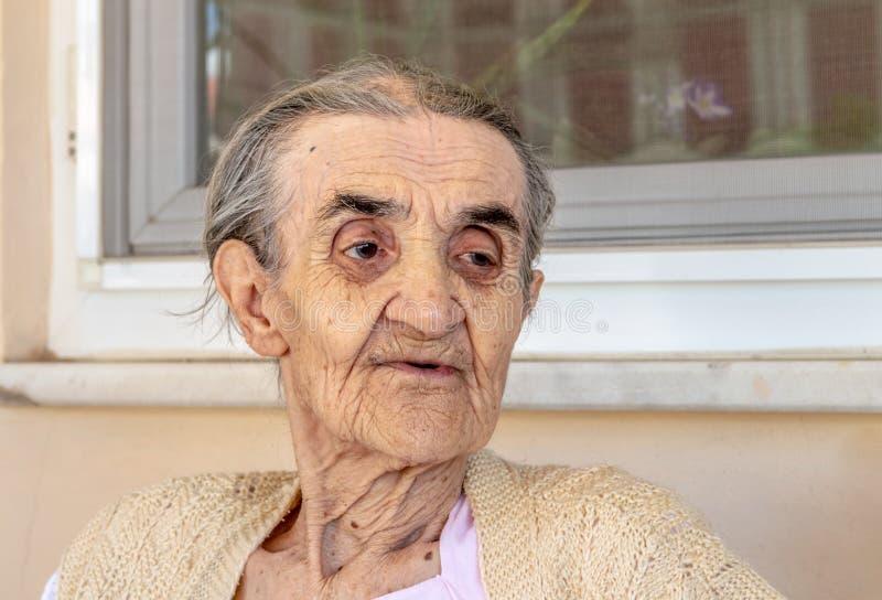 Donna senior molto anziana che si siede nel balcone un giorno di estate immagine stock libera da diritti