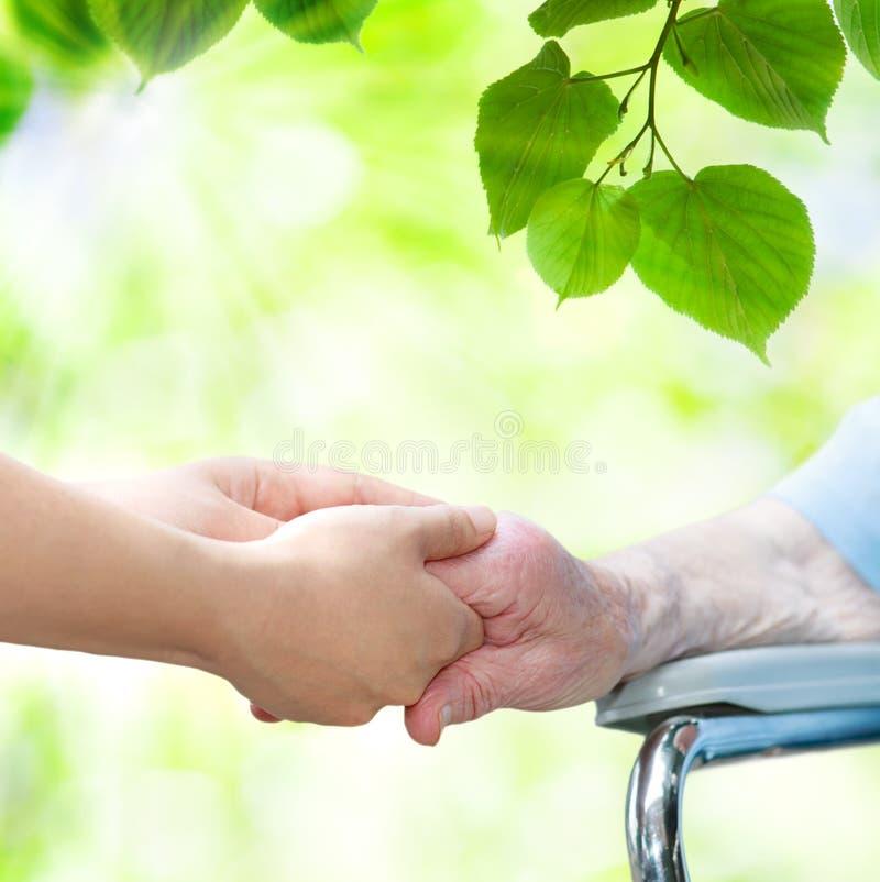 Donna senior nella sedia a rotelle che si tiene per mano con il giovane guardiano immagini stock